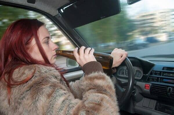 woman drinking in car